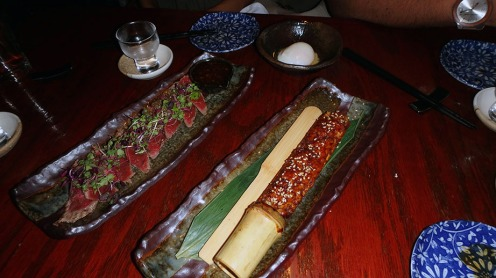 Back: Filet Mignon Tataki - All natural filet mignon, thinly sliced and lightly seared (rare): Ginger garlic soy sauce, Front: Tsukune Chicken - Japanese chicken meatball on bamboo served with soft egg dipping sauce